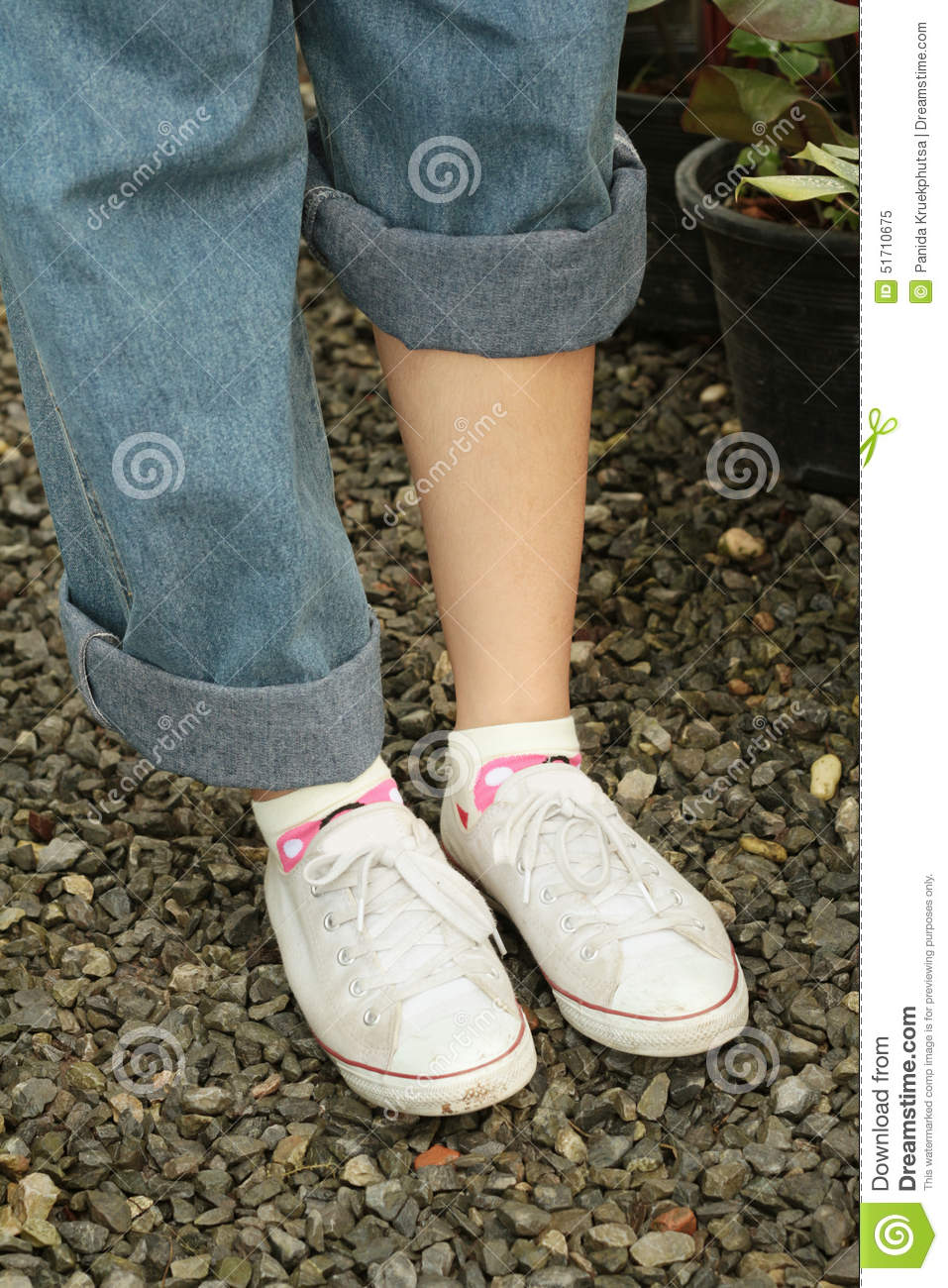 women wearing white shoes with blue jeans stock photo