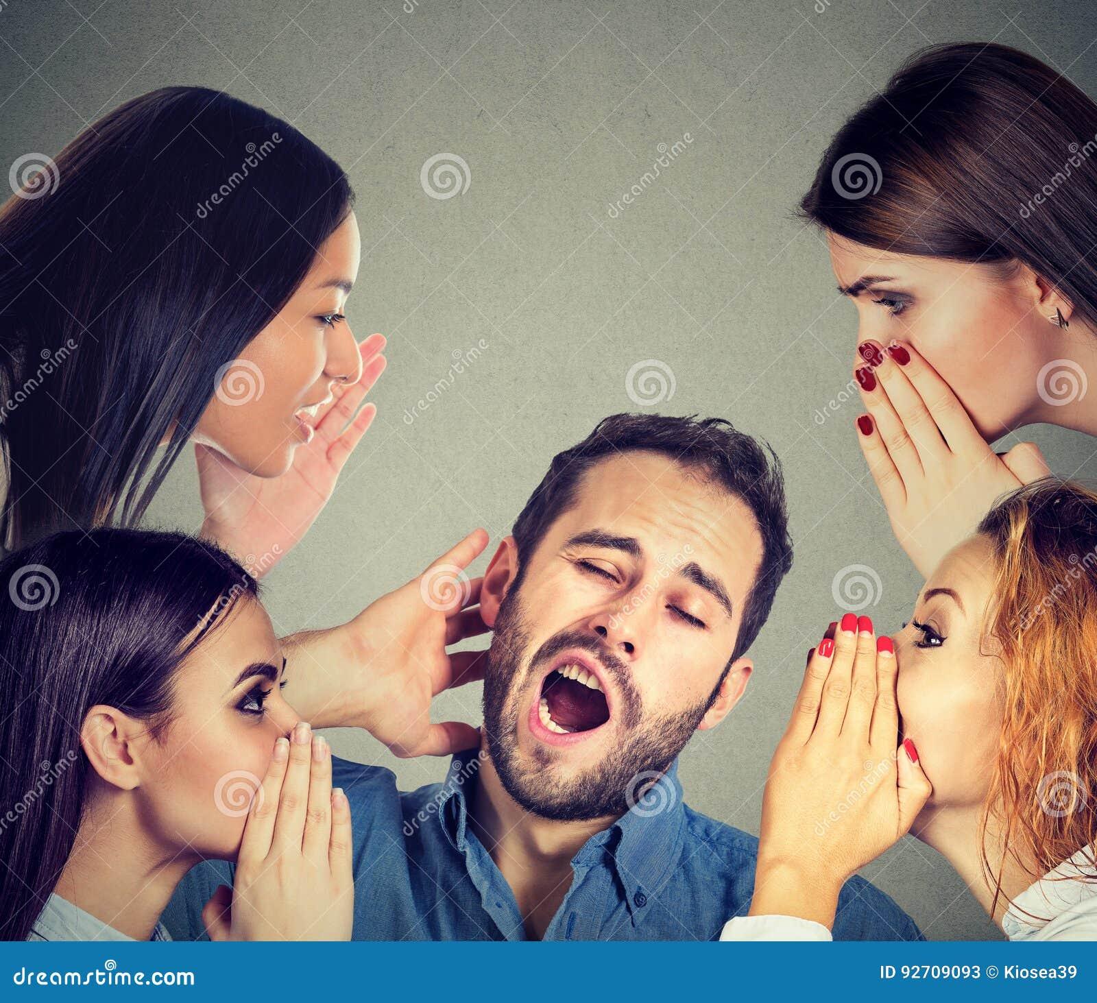 Women whispering a secret latest gossip to a bored sleepy man