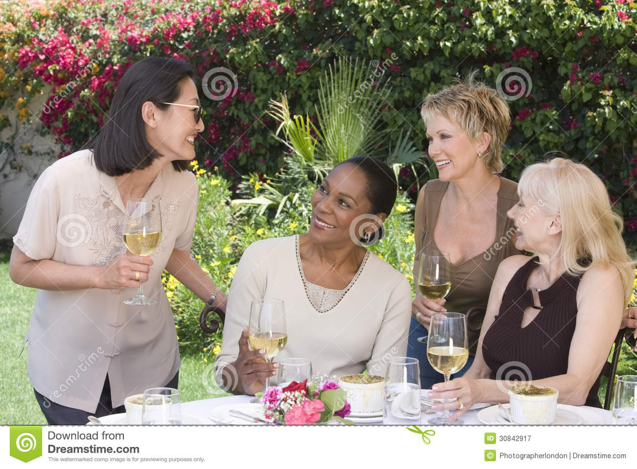 Women With Wine Glasses Chatting At Garden Party