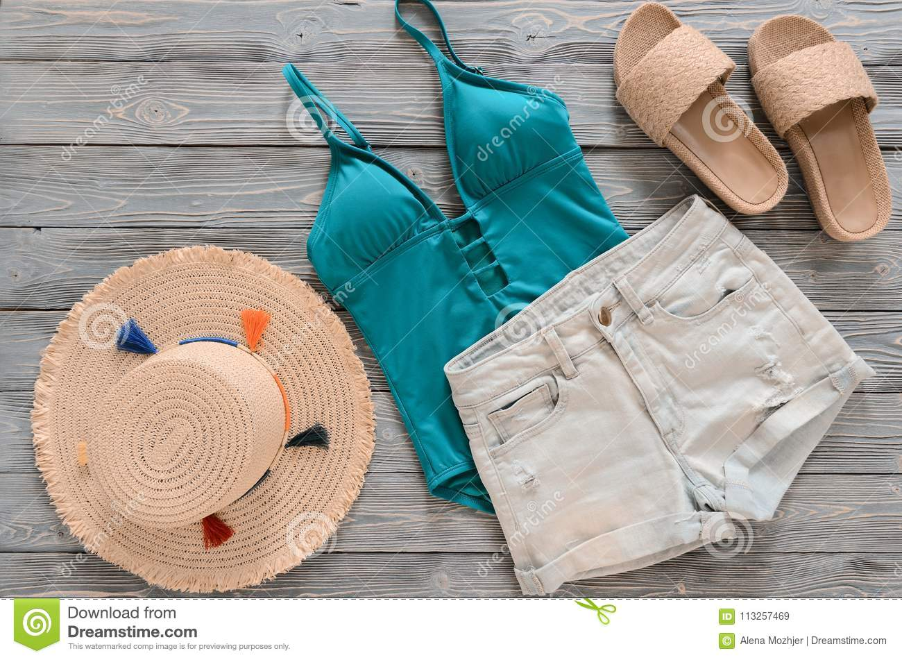 813be407ab Womens clothing, accessories denim shorts, straw hat, swimsuit, sandals on  grey wooden background. Trendy fashion outfit. Shopping, travel, summer,  beach ...