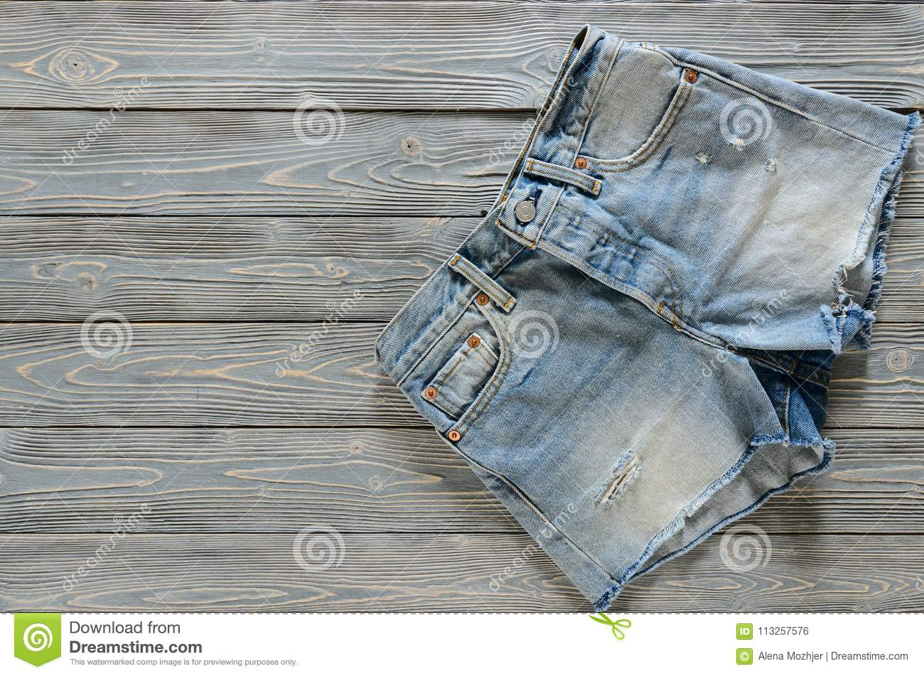 e75d236883 Womens clothing denim shorts on grey wooden background with copy space.  Trendy fashion outfit. Shopping concept. Mock up for online store. Flat lay.