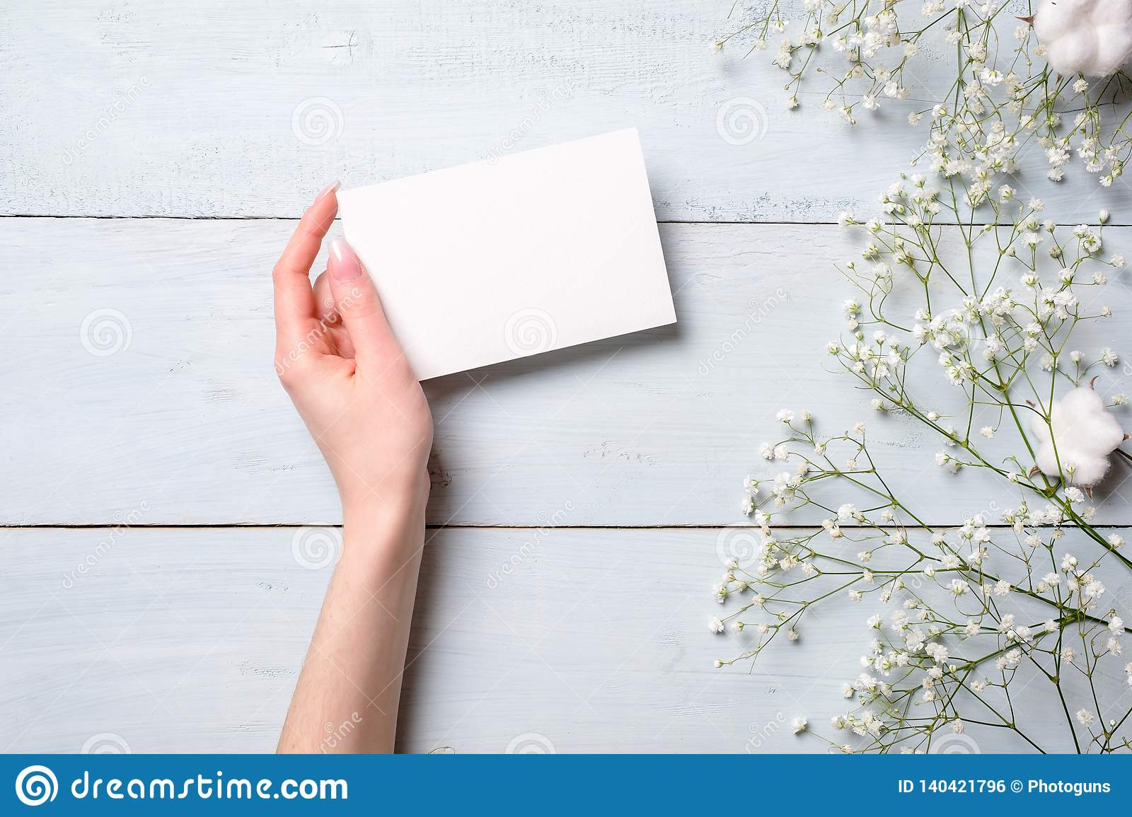 Womens hand holding blank paper card on light blue wooden background. Rustic table with flowers, wedding invitation card, letter,