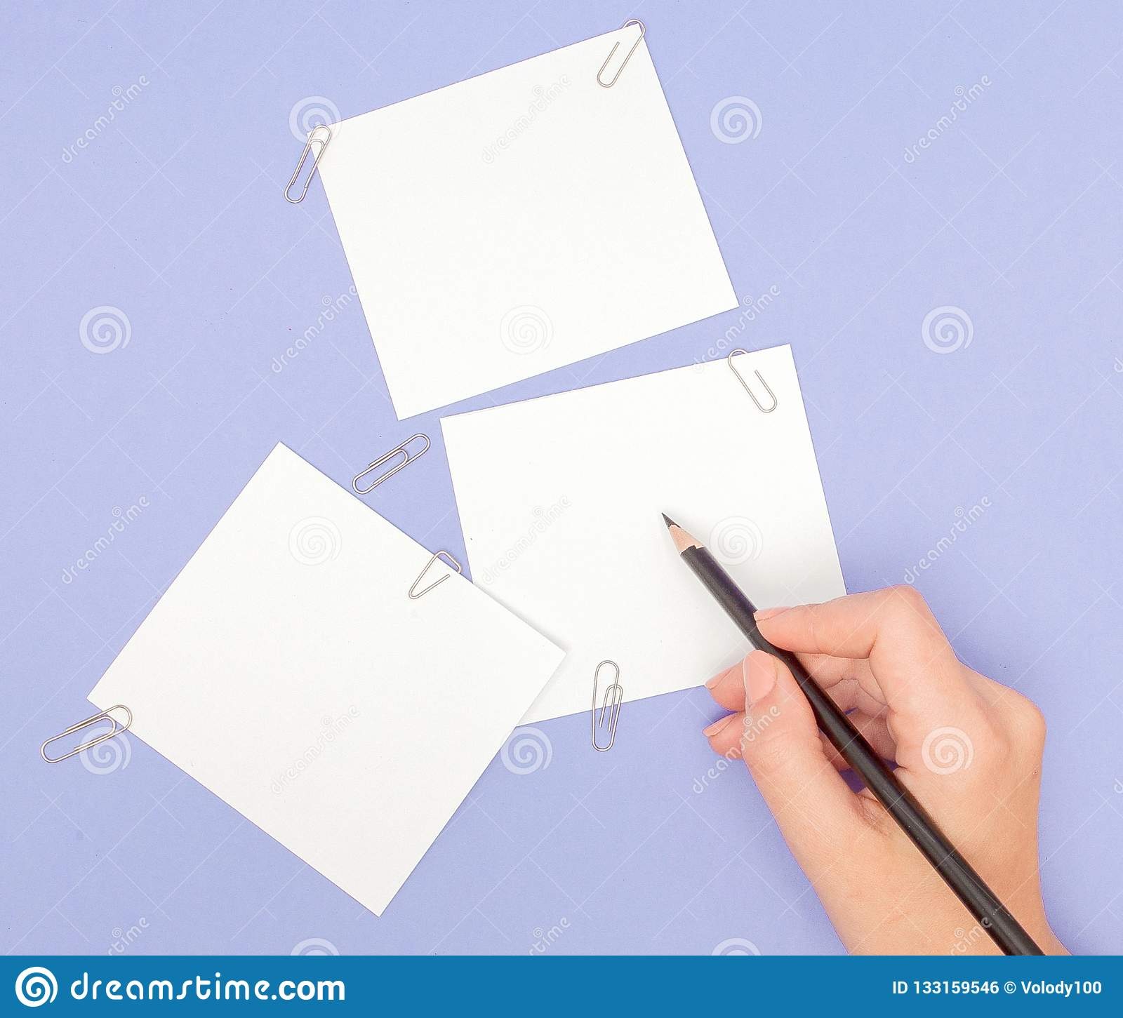 Womens hand writing on note papers on purple background. Blanks sheet of papers and color pencils on violet background