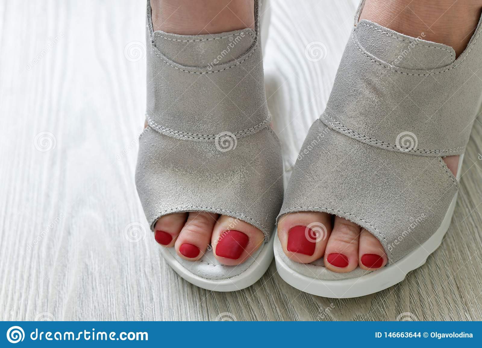 The Womens legs in summer white sandals
