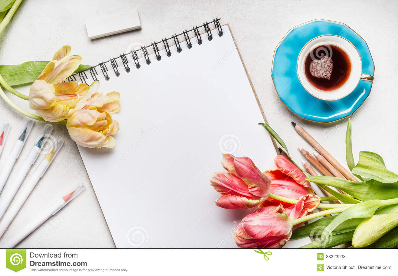Womens springtime workspace with pretty tulips, notebook or sketchbook , colorful brush markers and coffee cup