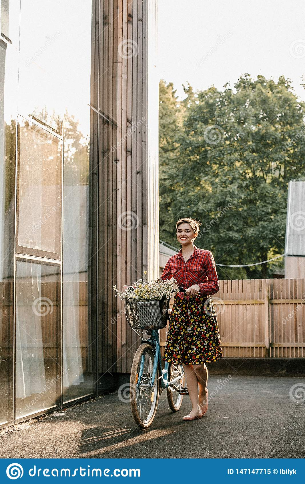 A wonderful girl travels by bike. Walking in the outdoors. Beautiful woman with a basket of flowers. Bike ride