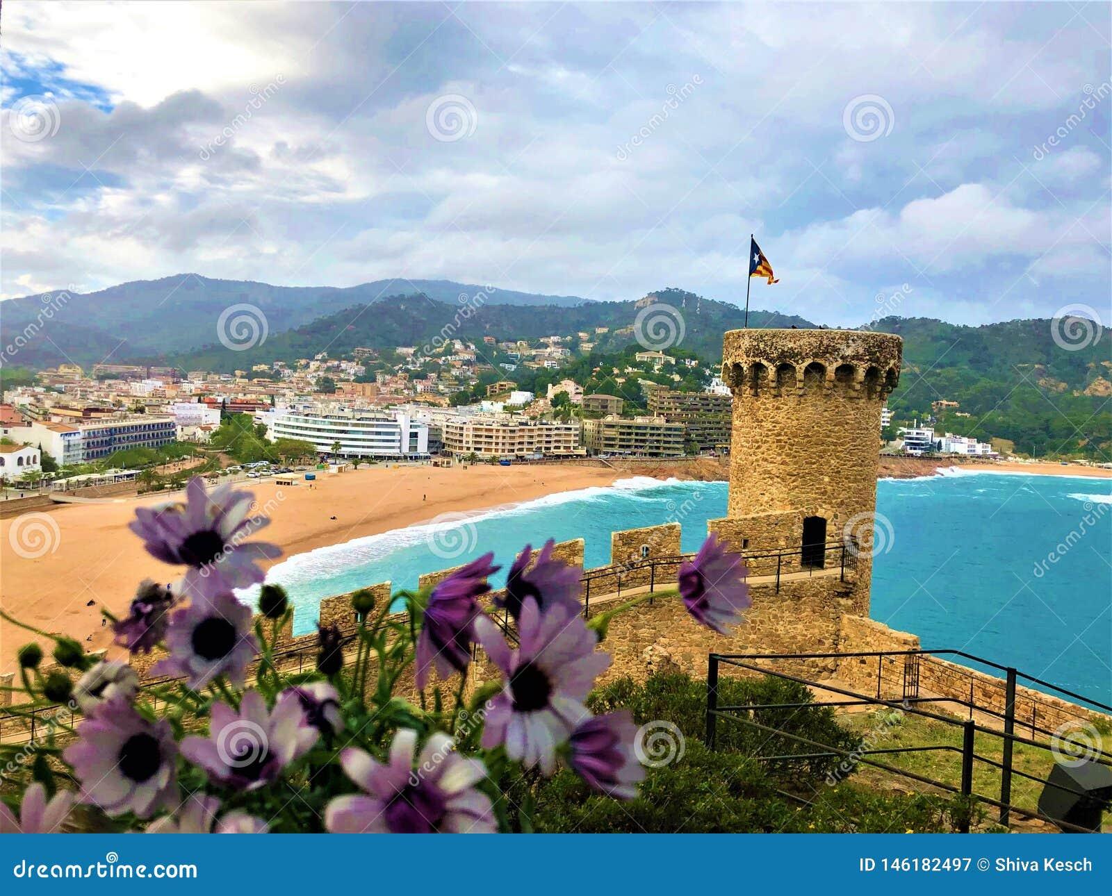 Wonderful landscape in Tossa de Mar, Spain. Medieval tower, beach, sea and flowers
