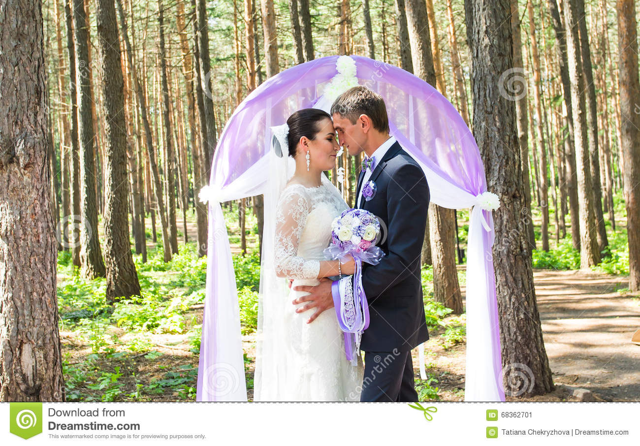 Wonderful stylish rich happy bride and groom standing at a wedding ceremony in green garden near purple arch with