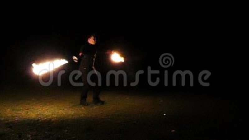 Juggler beats two lit torches and gets a lot of sparkles at night in slo-mo