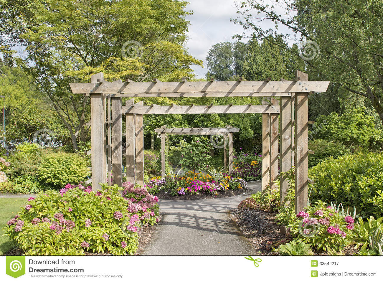 Wood Arbor Over Garden Path with Plants Trees and Flowers Blooming in ...