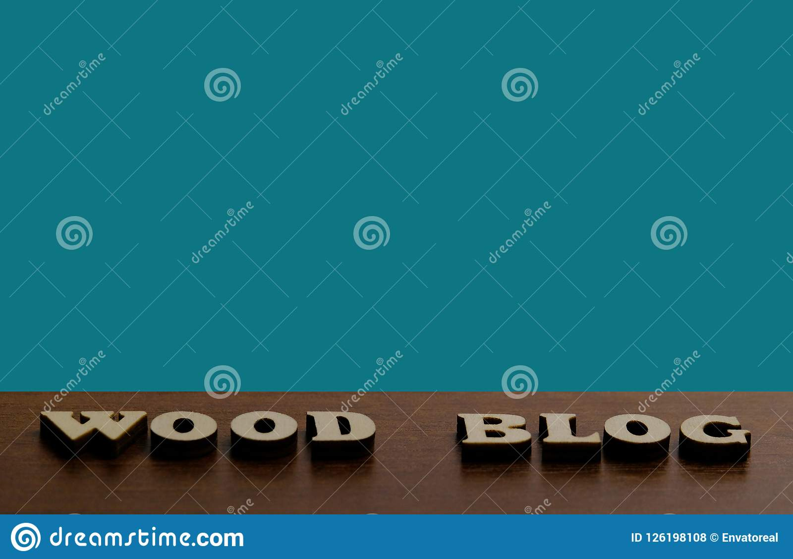 WOOD BLOG. An inscription made of wooden letters against the texture of a dark brown wood. Blue background for copy space.