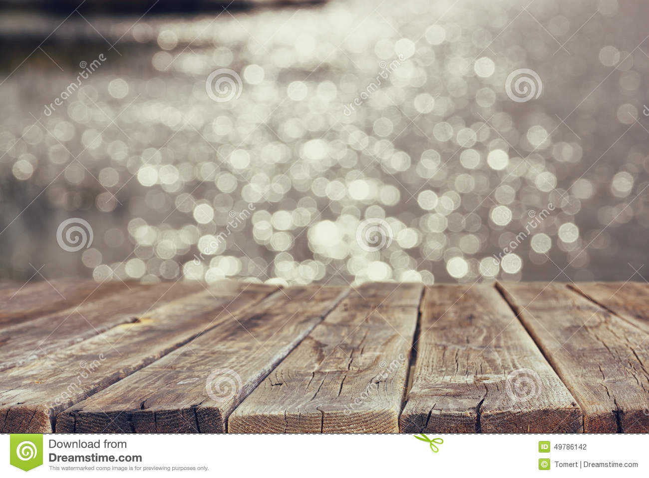 Wood board table in front of summer landscape of sparkling lake water ...