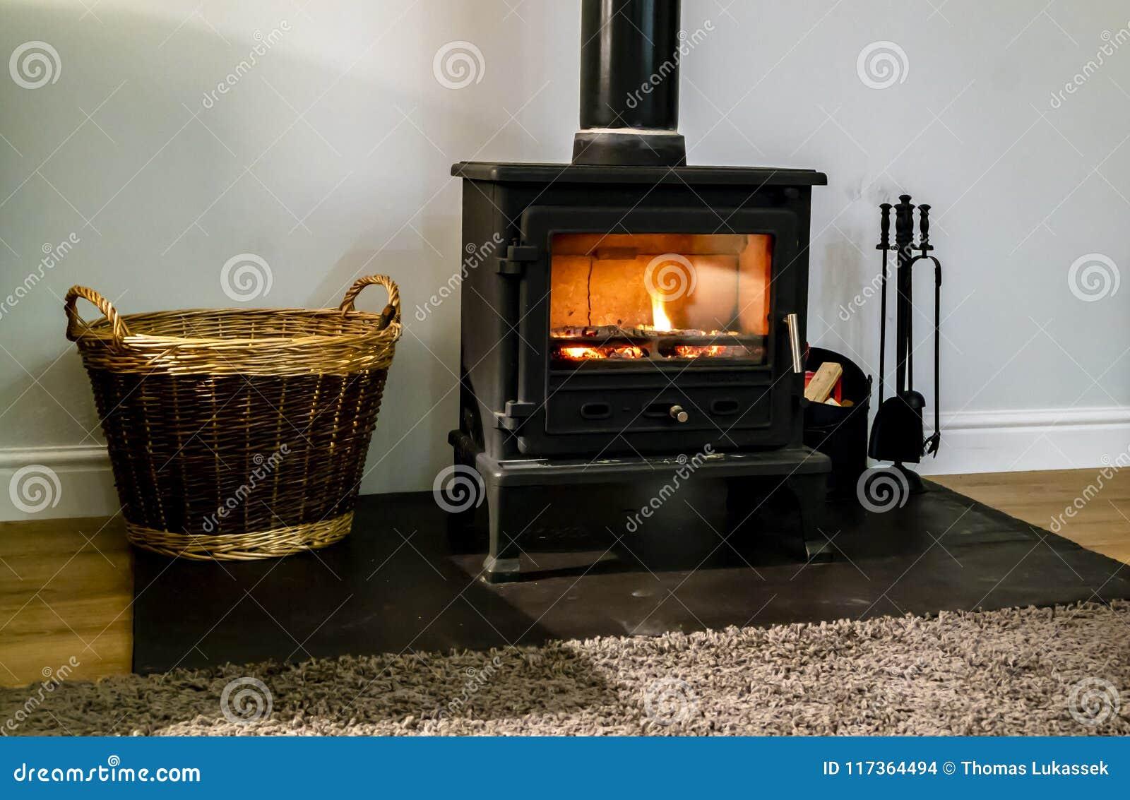 Wood brinnande spis med den glass dörren