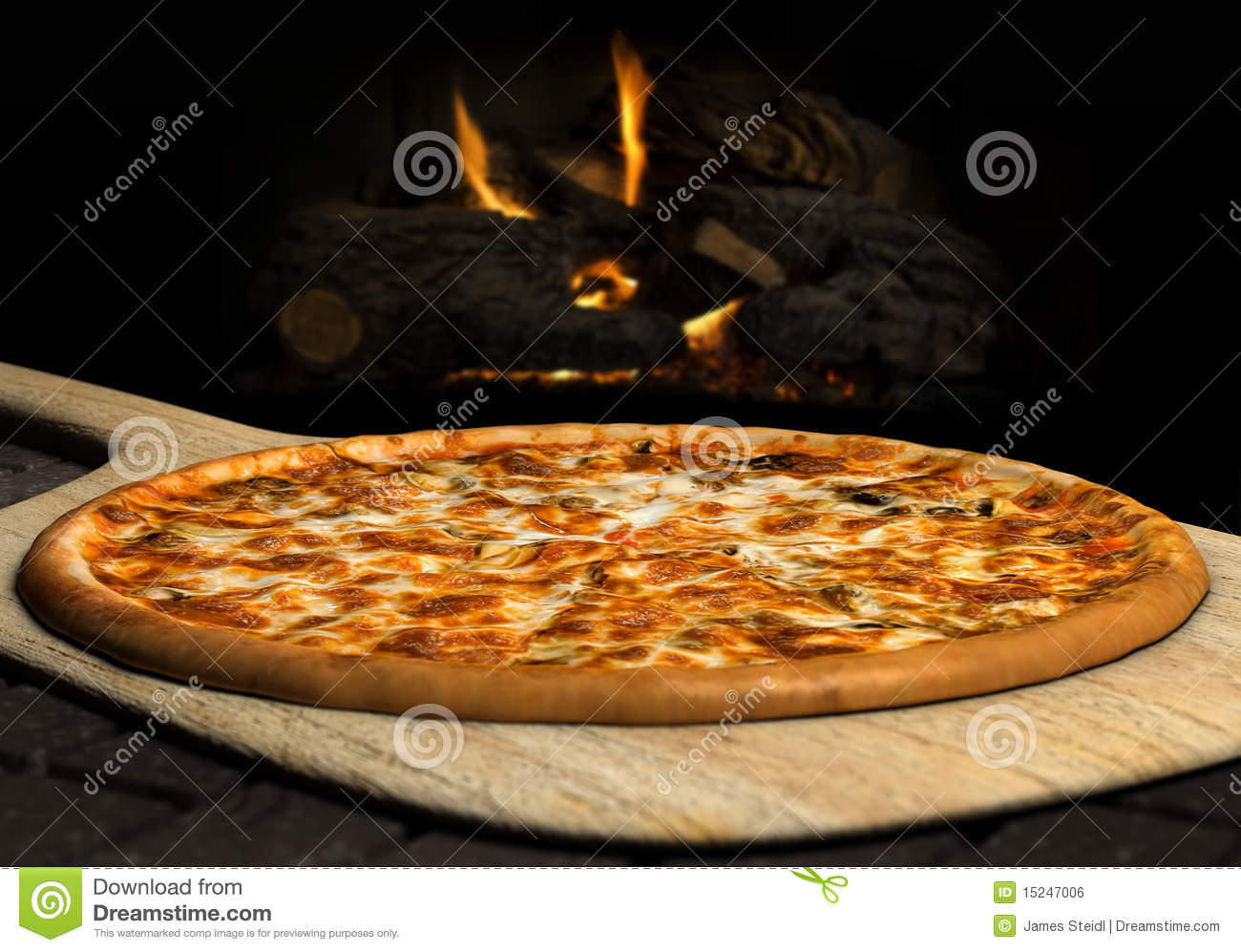 Pizza resting on a pizza peel near an open fire.