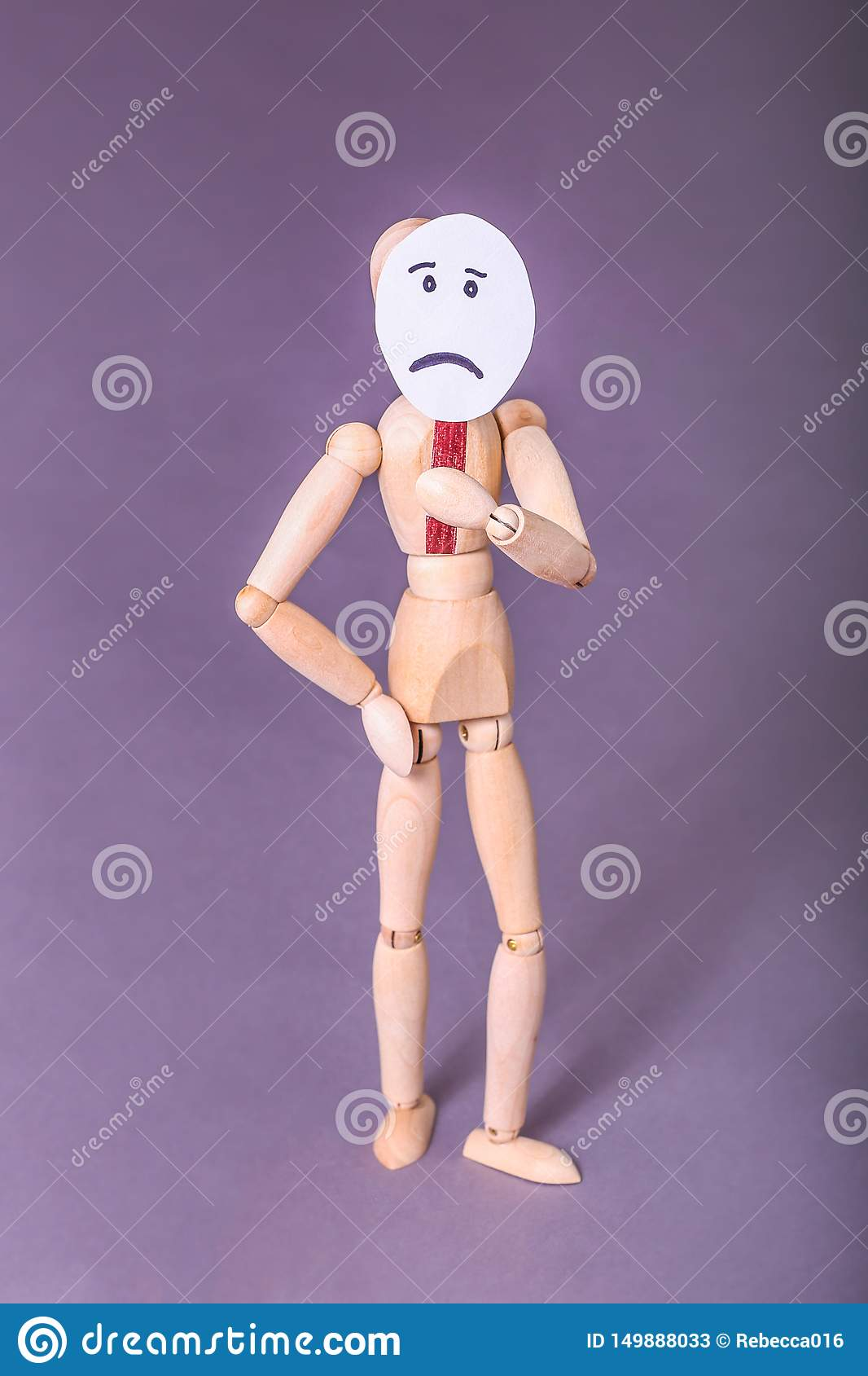 Wooden manikin standing with one hand on hip one hand holding up a sad face sign over his face