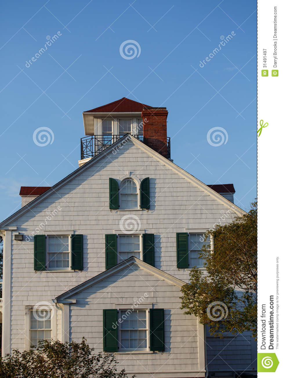 wood siding coastal home with green shutters stock image