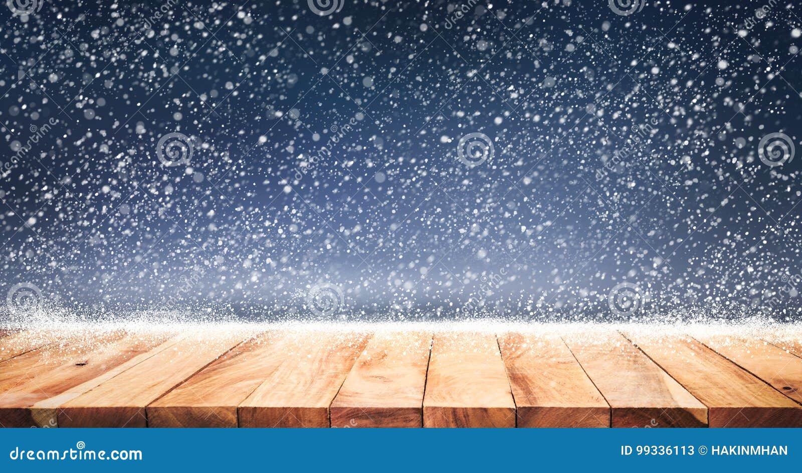 Wood table top with snowfall of winter season background.christmas