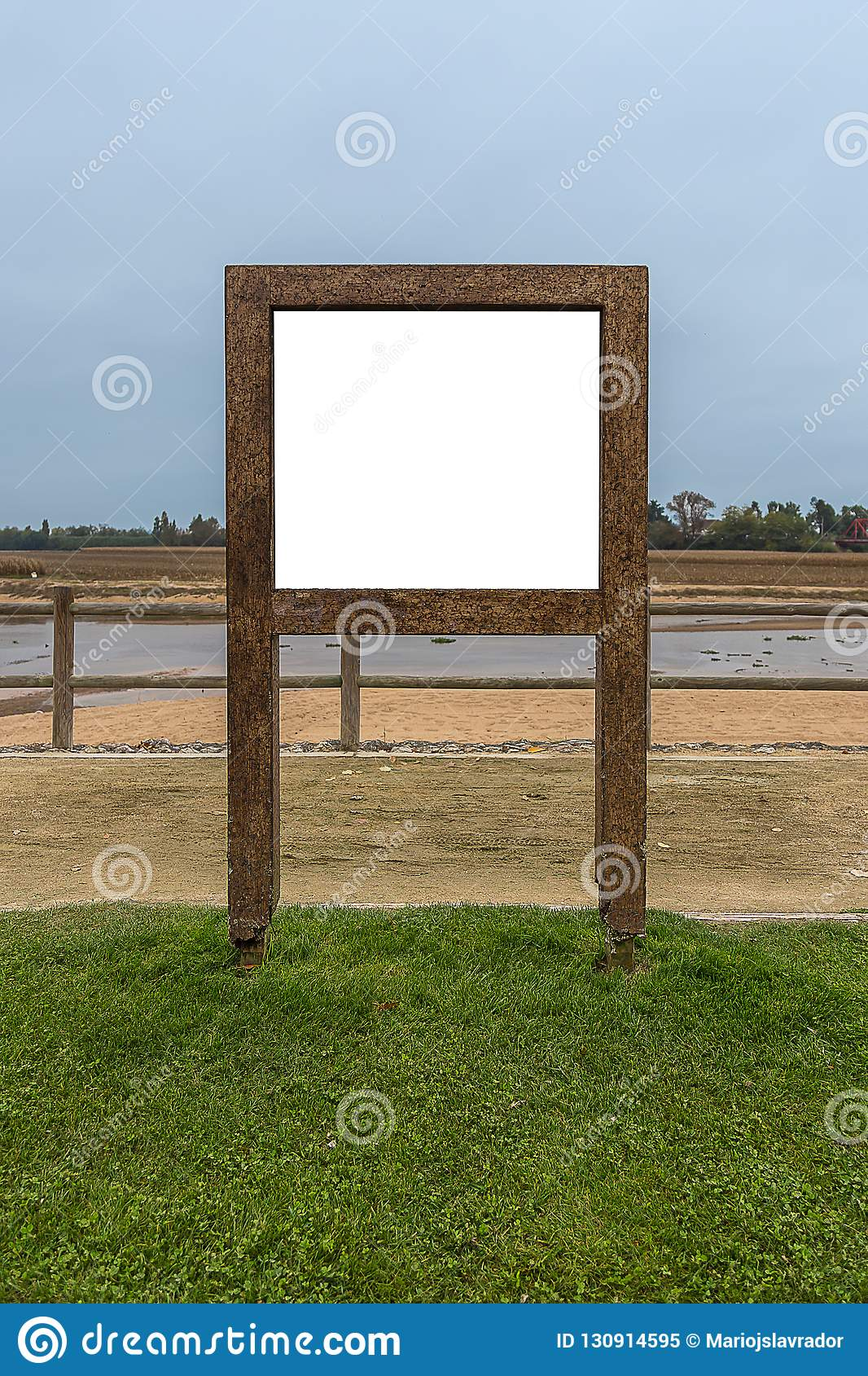 Wooden Advertising Frame By The River, in a Grass Field Under a Pale Sky