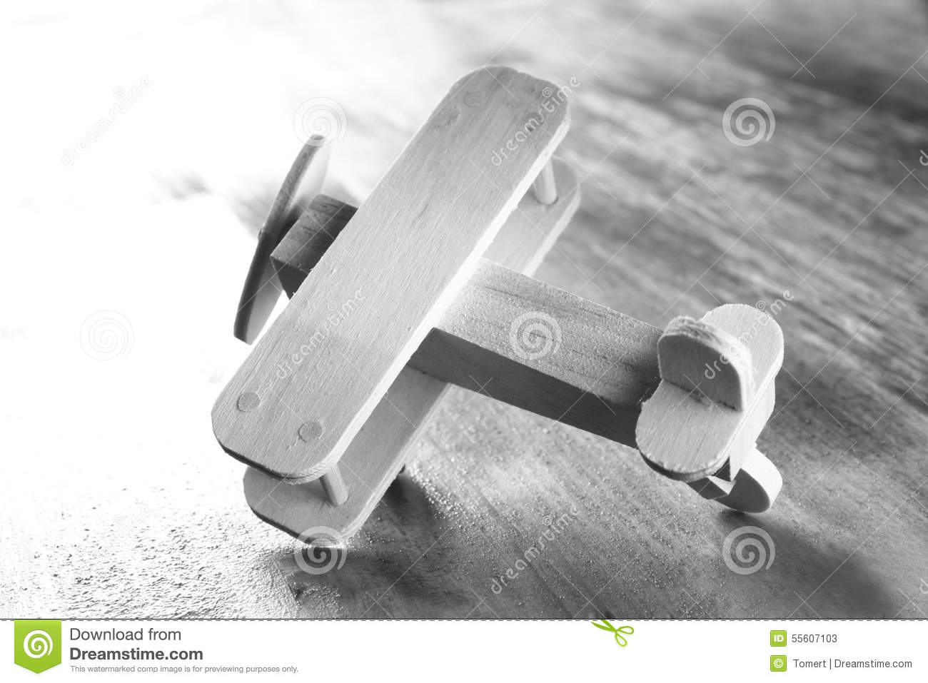 Wooden airplane toy over textured wooden background. retro style image. black and white old style photo