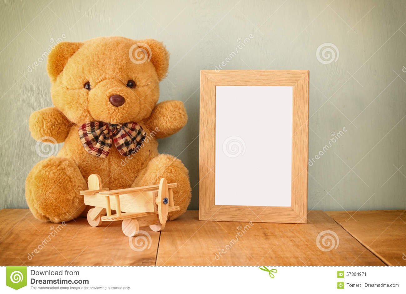Wooden airplane toy and teddy bear over wood table next to blank photo frame. retro filtered image. ready to place photography