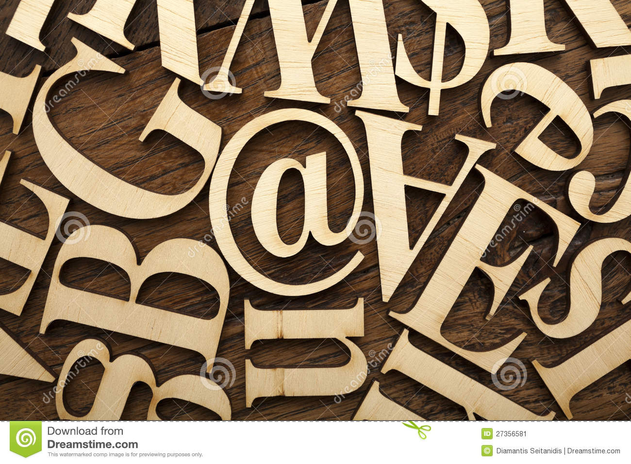 Wooden alphabet letters on old wooden surface.