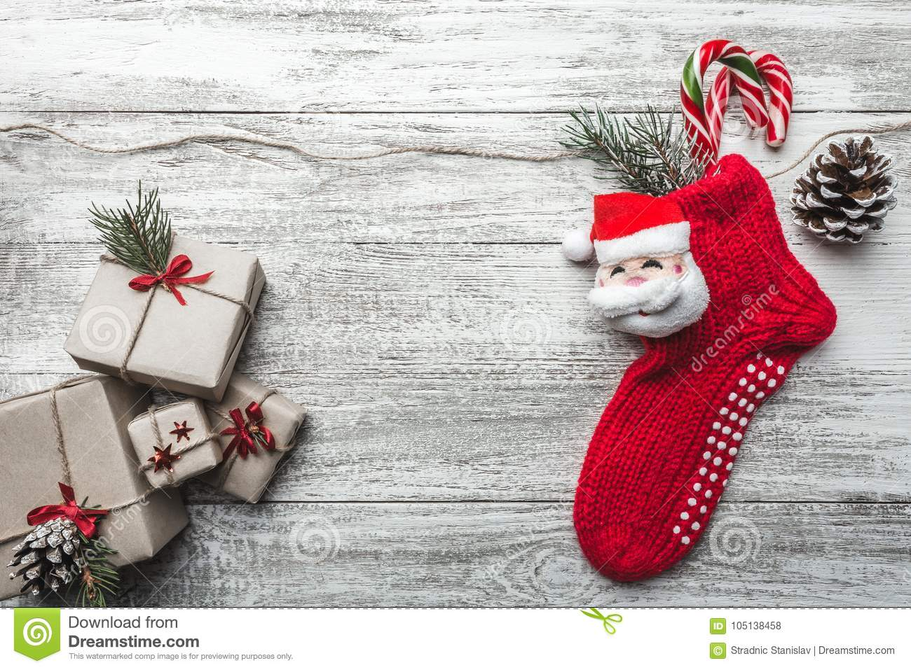wooden background painted white with a christmas sock and santa claus fir tree and