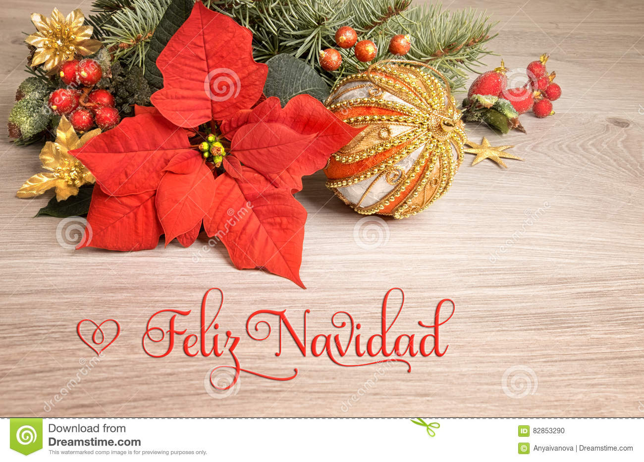 wooden background with poinsettia and decorated christmas tree twigs text on the picture means merry christmas in spanish