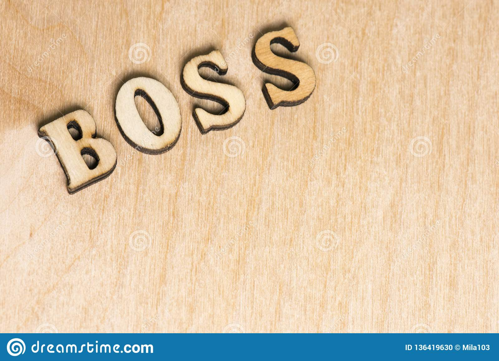On a wooden background word, the label boss of wooden letters