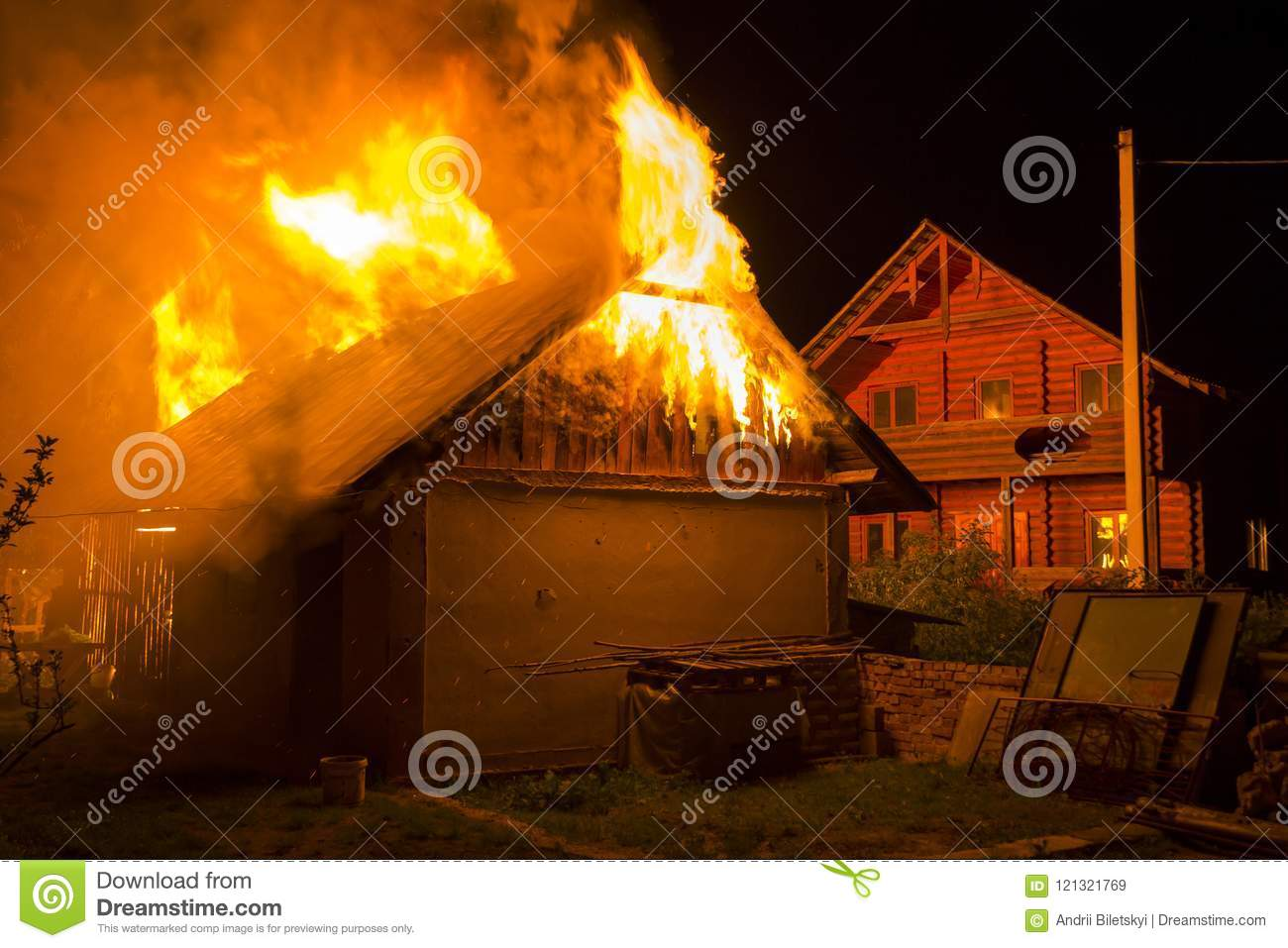 Wooden barn burning at night. High orange fire flames, dense smoke from under tiled roof on dark sky, trees silhouettes and reside