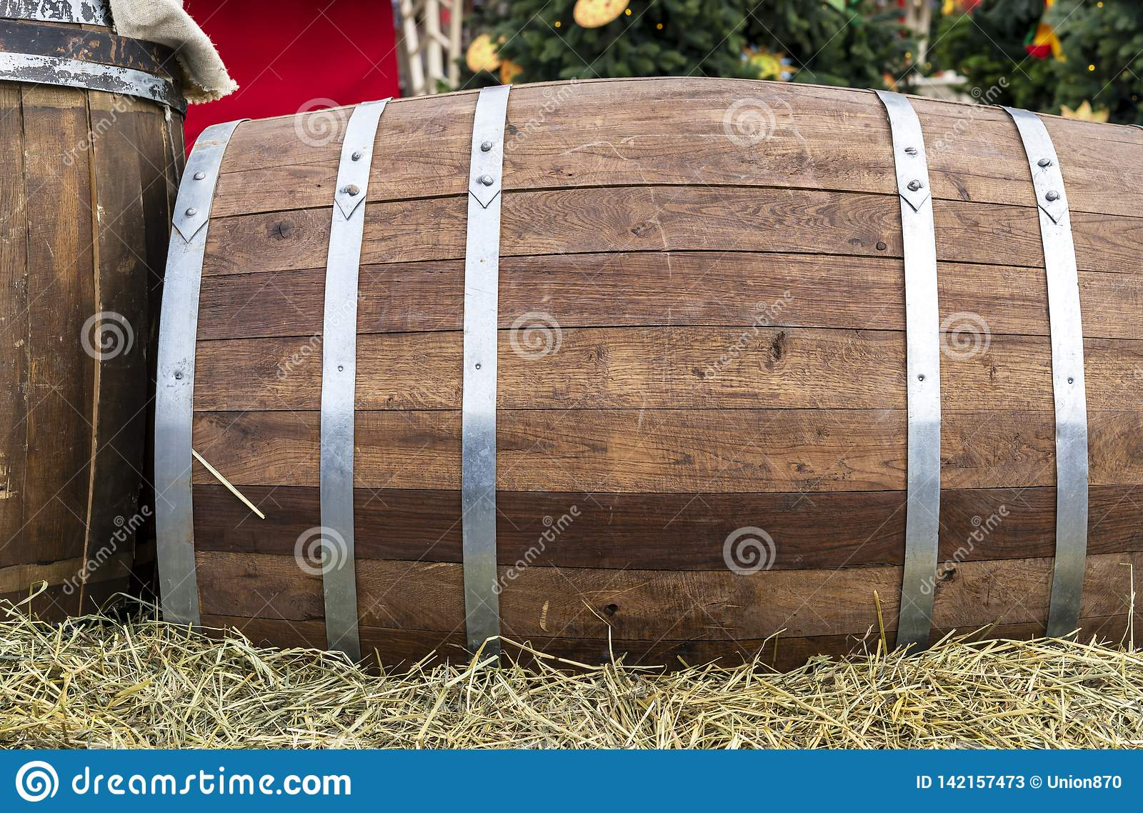 Wooden barrel with metal hoops. Oak barrel on straw