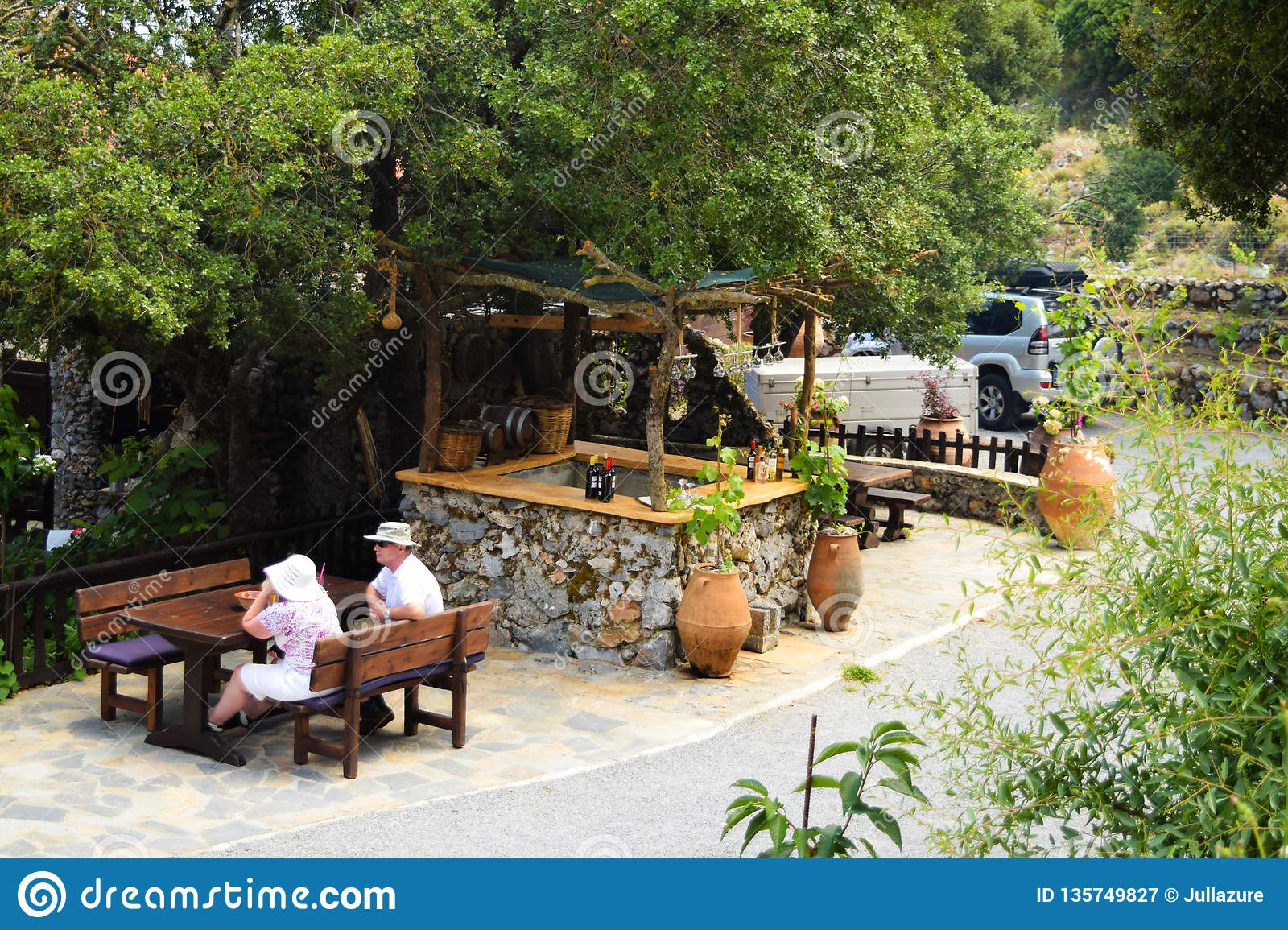 Crete, Greece - June 22, 2015: Wooden barrel of wine and table in outdoor cafe. Street cafes in Crete, Greece