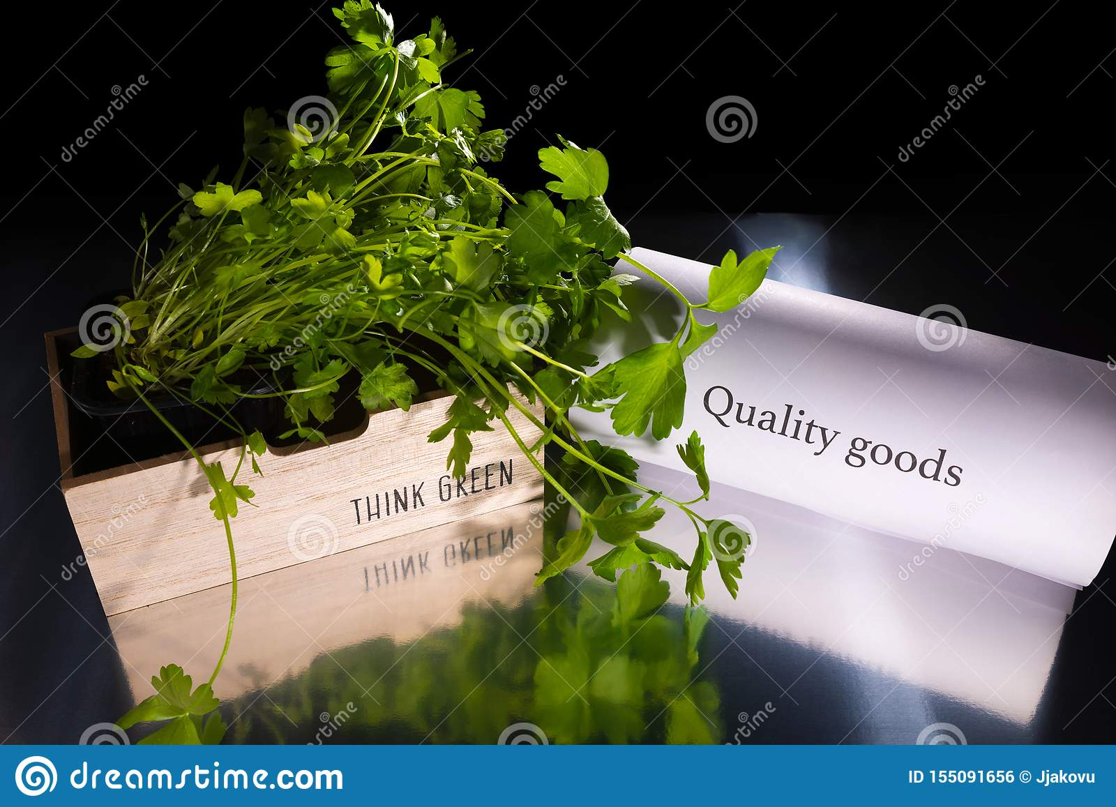Wooden basket with green plant/parsley is on the transparent table/background. The basket has note `Think green`. Near the basket