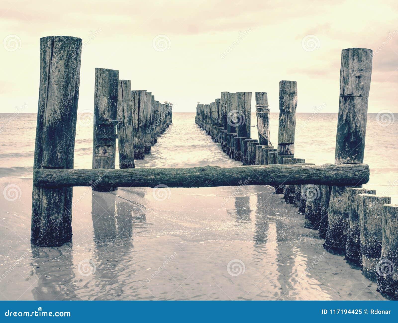 Wooden batten bridge juts out into expanse of sea. The famous tourist attraction