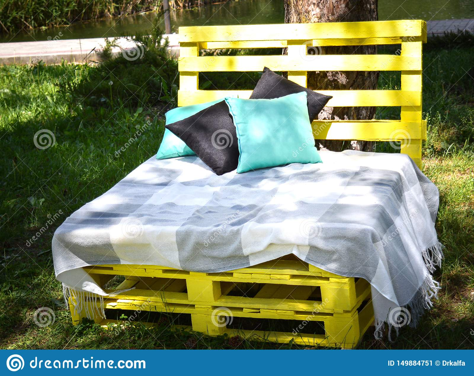 Wooden bench made of yellow pallets of freight cargo cases for sittin with pillows and plaid in the park. The concept of