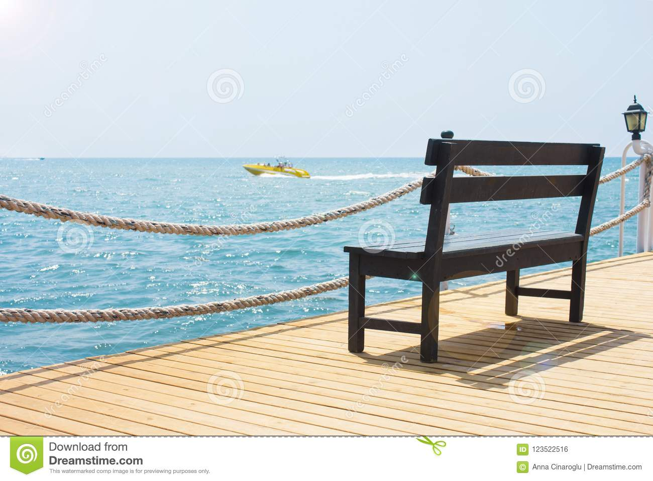 Marvelous Wooden Bench On The Pier By The Sea With A Boat Stock Photo Evergreenethics Interior Chair Design Evergreenethicsorg
