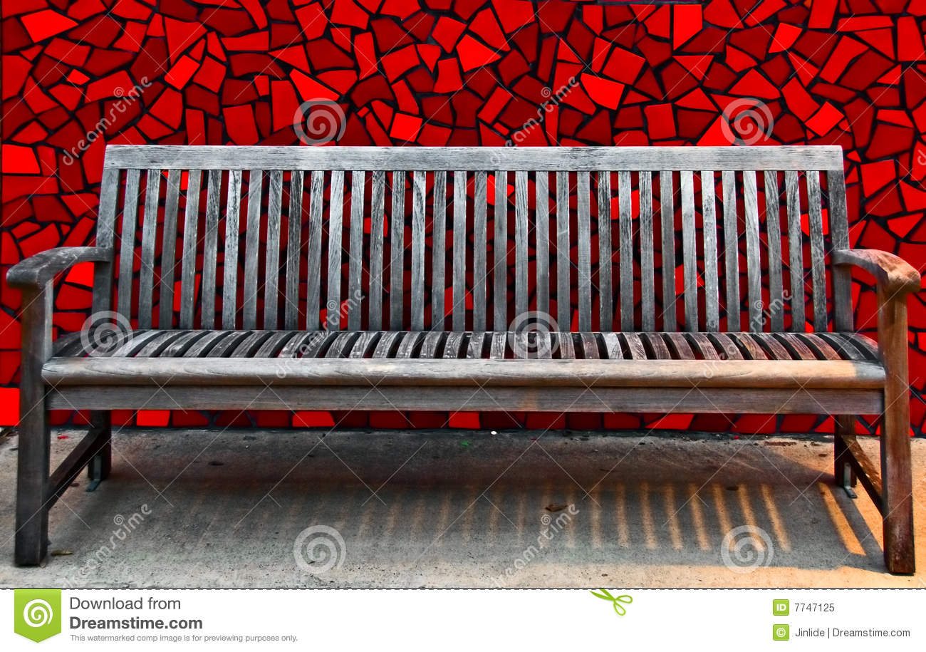 A wooden bench with red tile wall