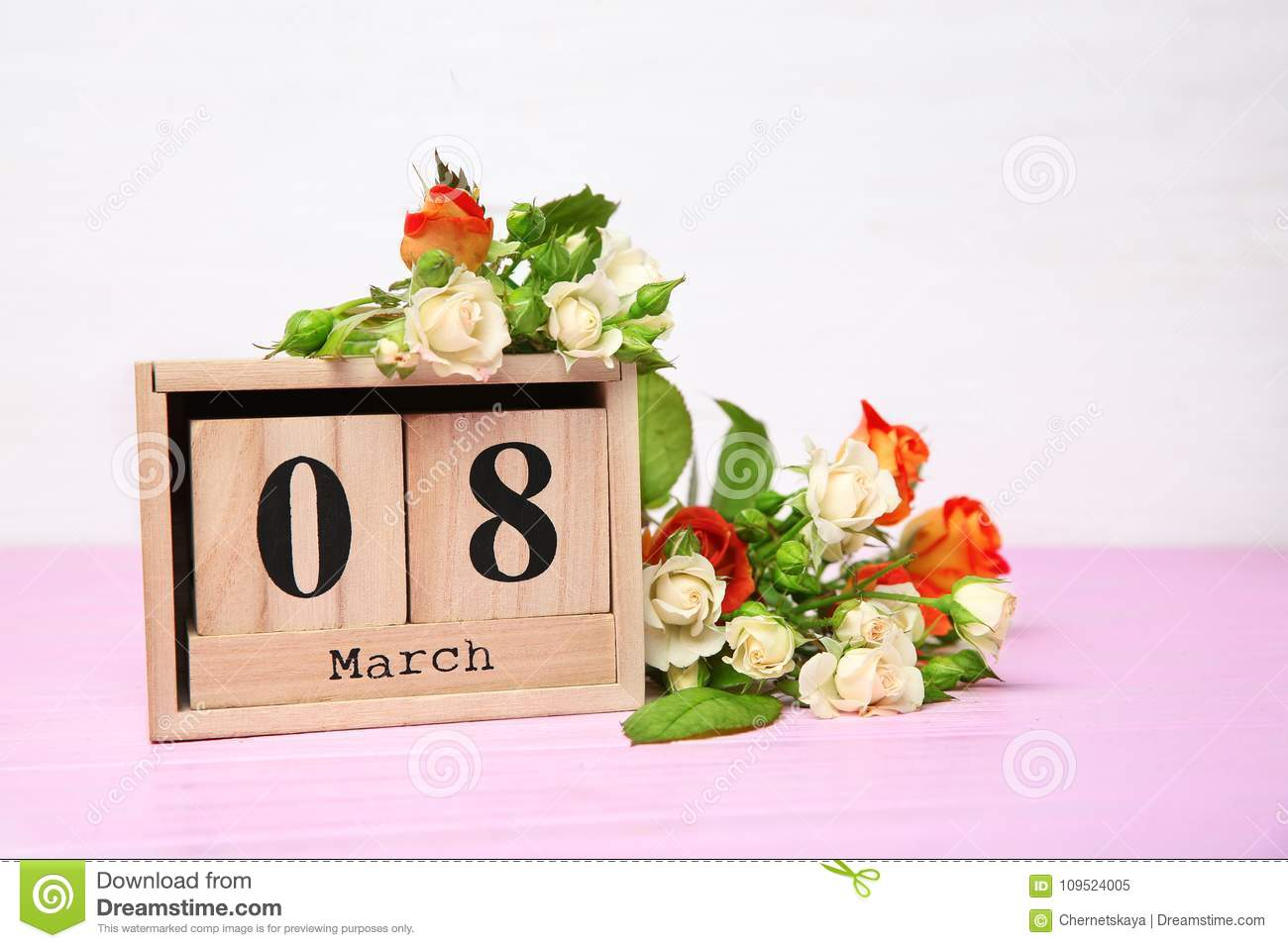 Wooden block calendar and roses on tabl