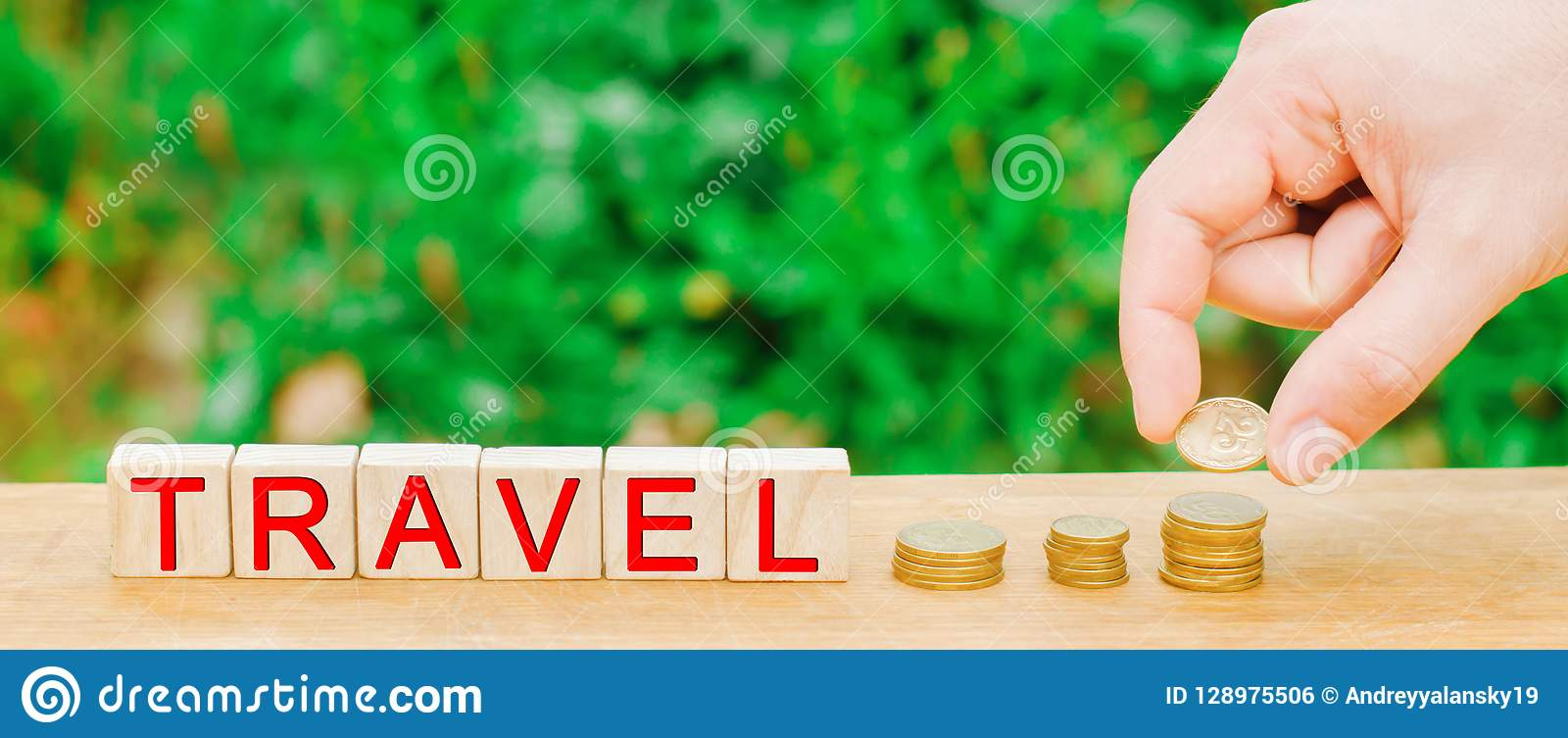 Wooden blocks and the inscription `travel` and a stack of coins. concept of saving and collecting money on travel. Budget for vaca