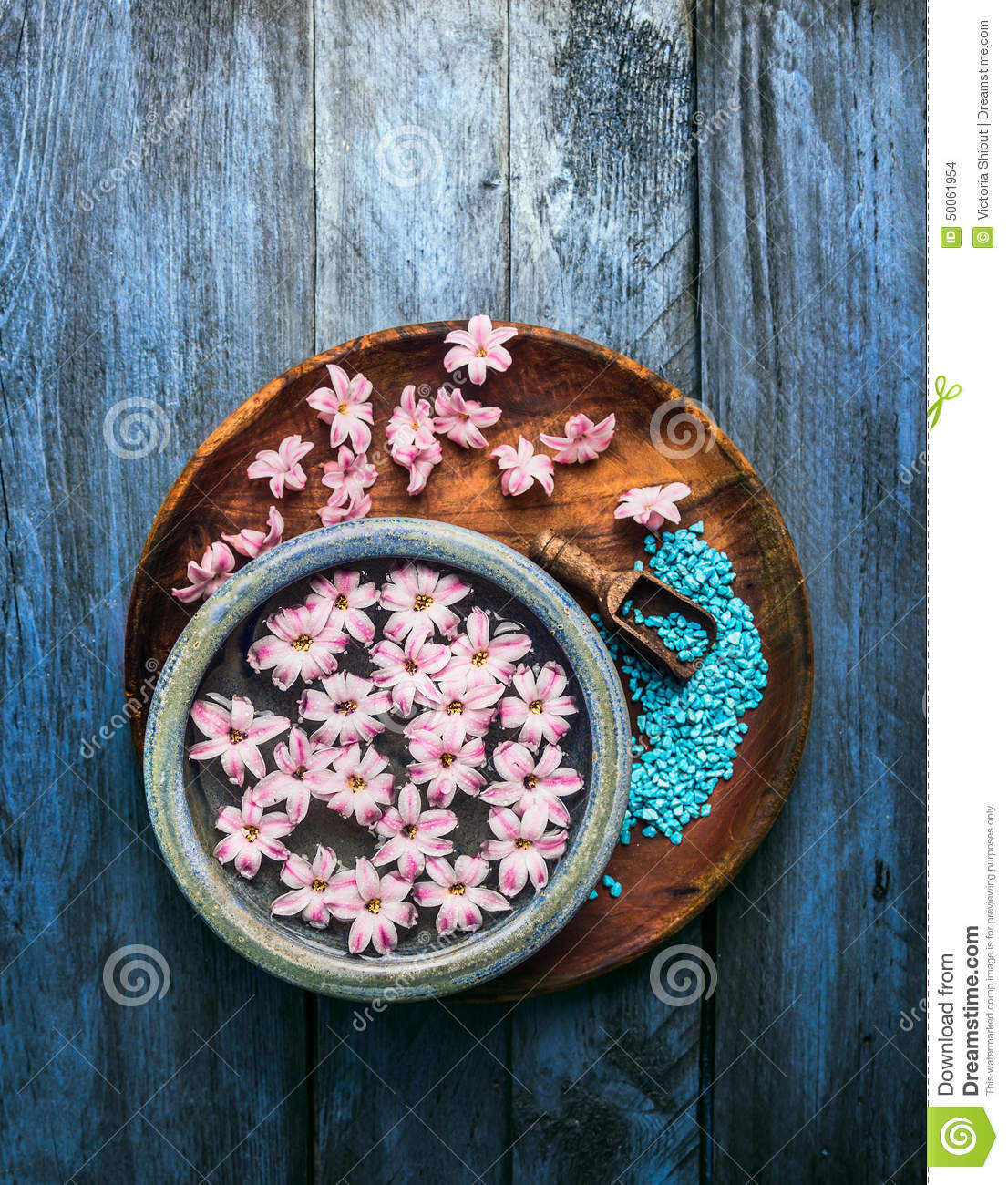 Wooden and blue bowl with pink flowers and water, scoop with sea salt on old background