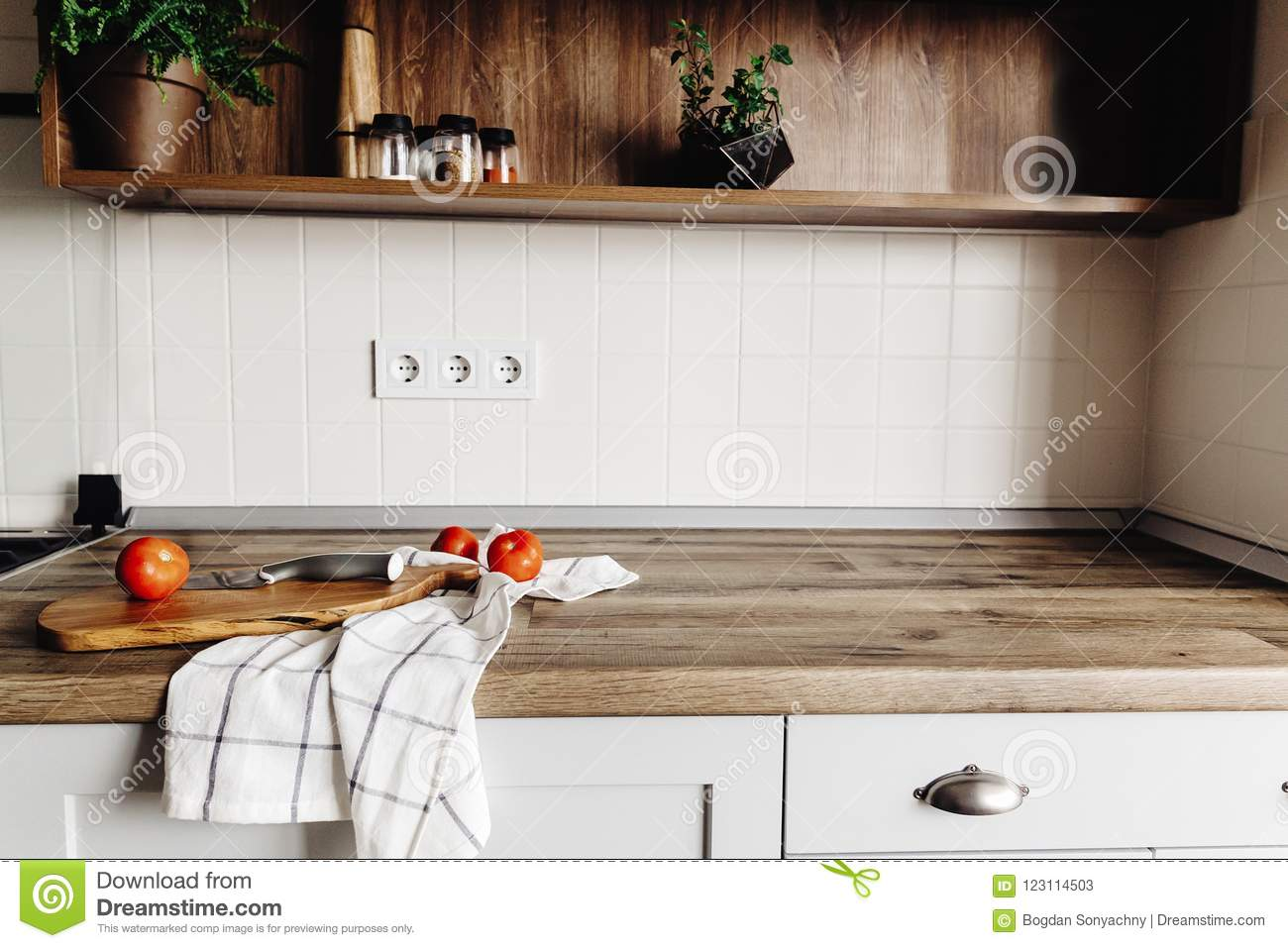 Wooden board with knife, tomatoes on modern kitchen countertop a