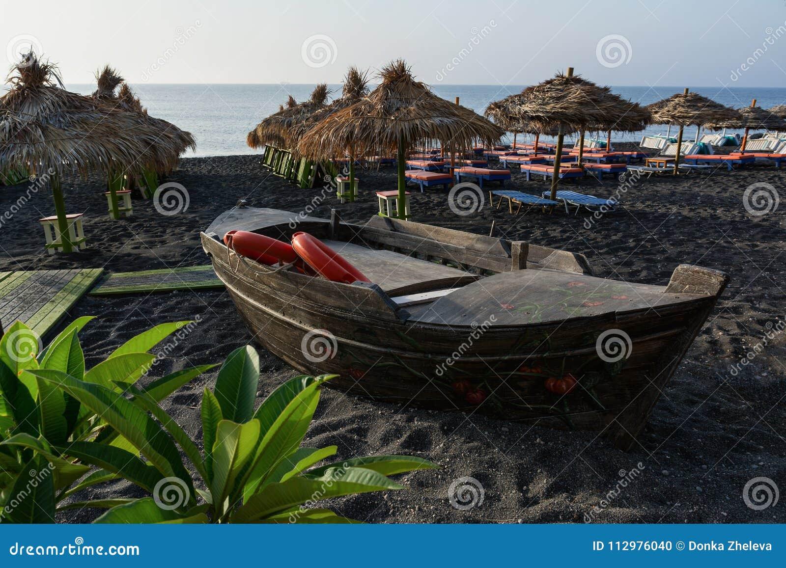 Wooden boat, tanning beds and straw umbrellas on Perissa beach, Santorini island, Greece