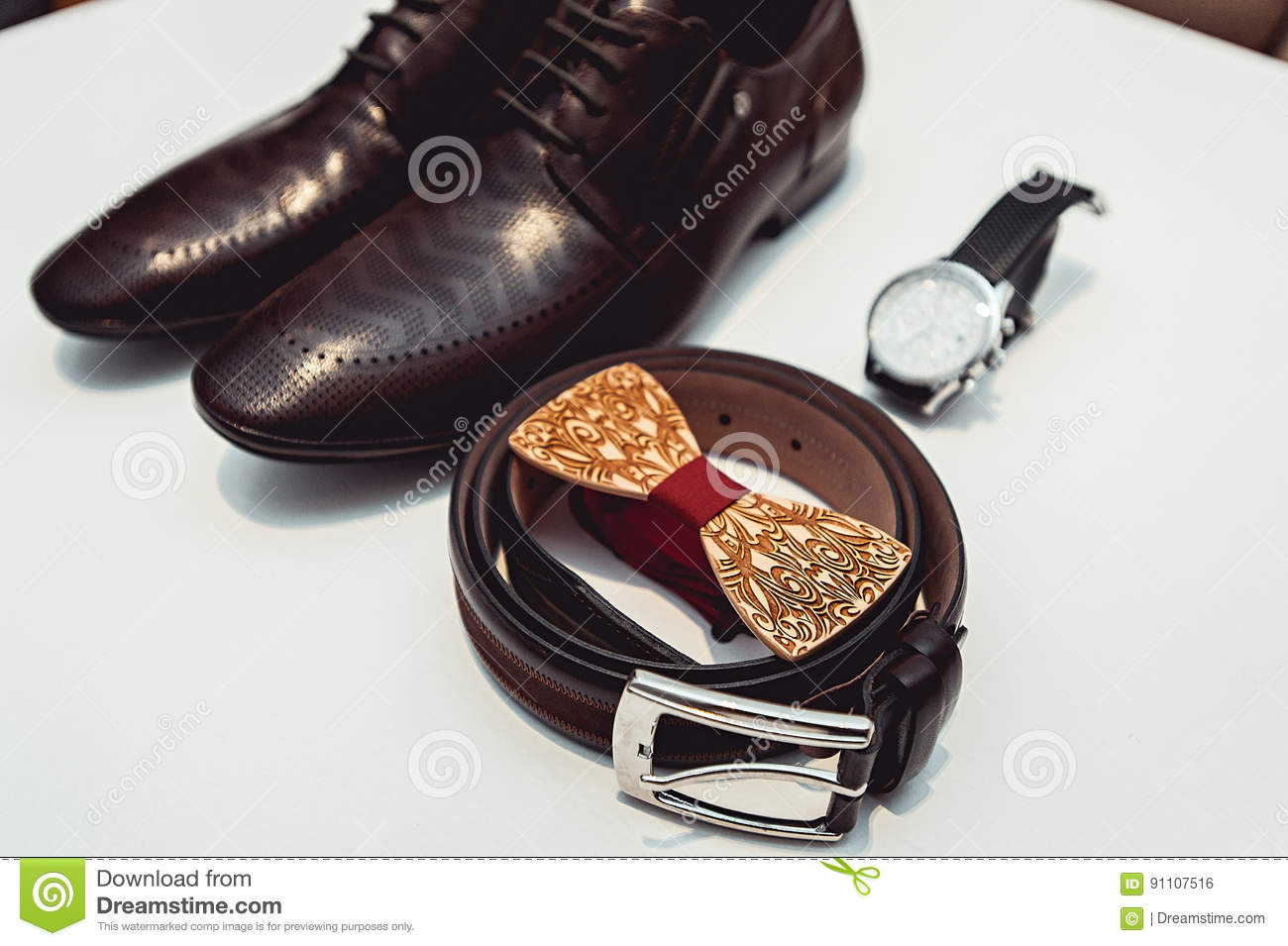 ec46dd6414be Wooden bow tie, brown leather shoes, belt, watch. Grooms wedding morning.  Close up of modern man accessories. Close up of modern man accessories on a  white ...