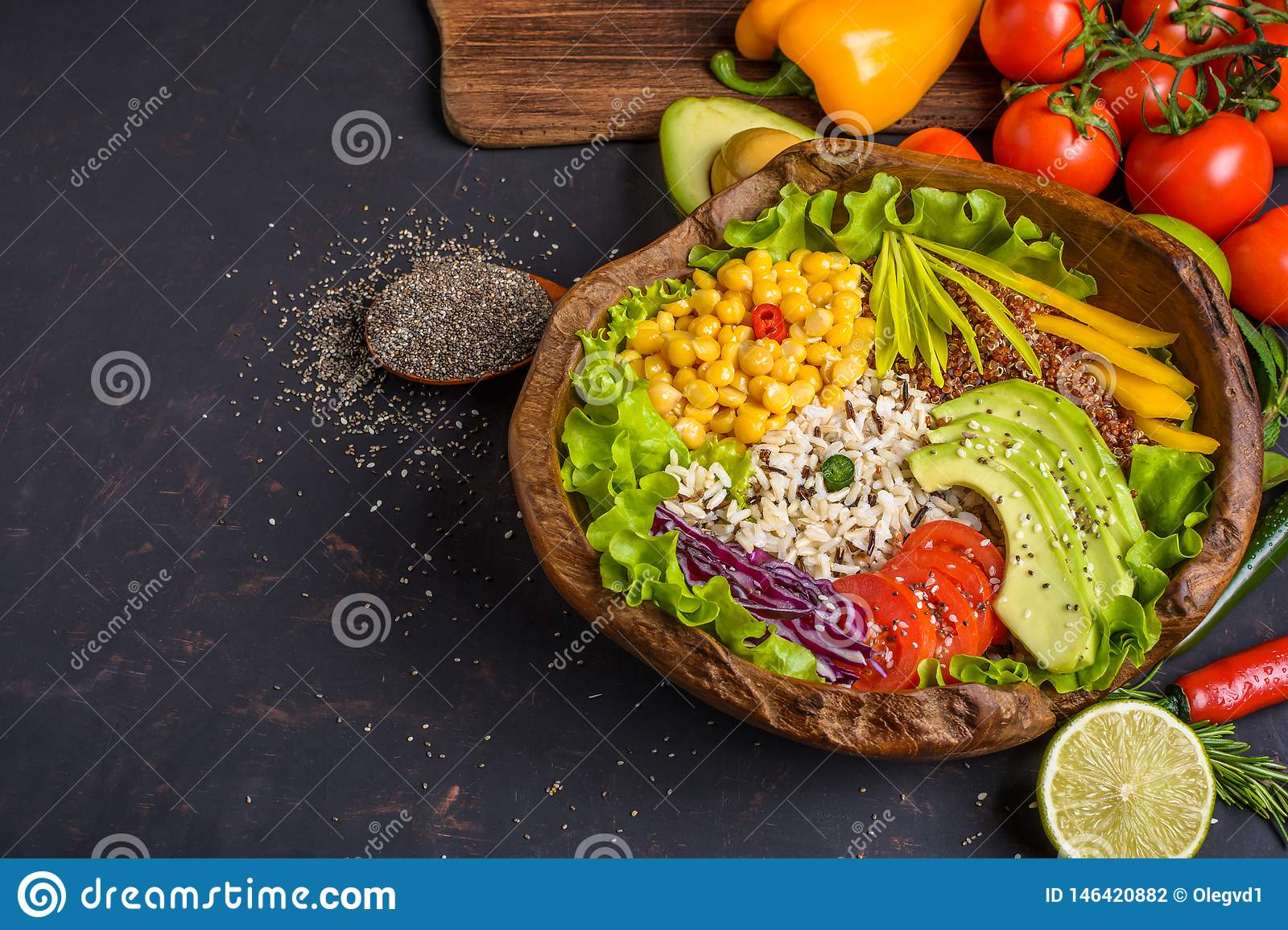 Wooden bowl with chickpea, avocado, wild rice, quinoa, bell pepper, tomatoes, greens, cabbage, lettuce on dark stone table and