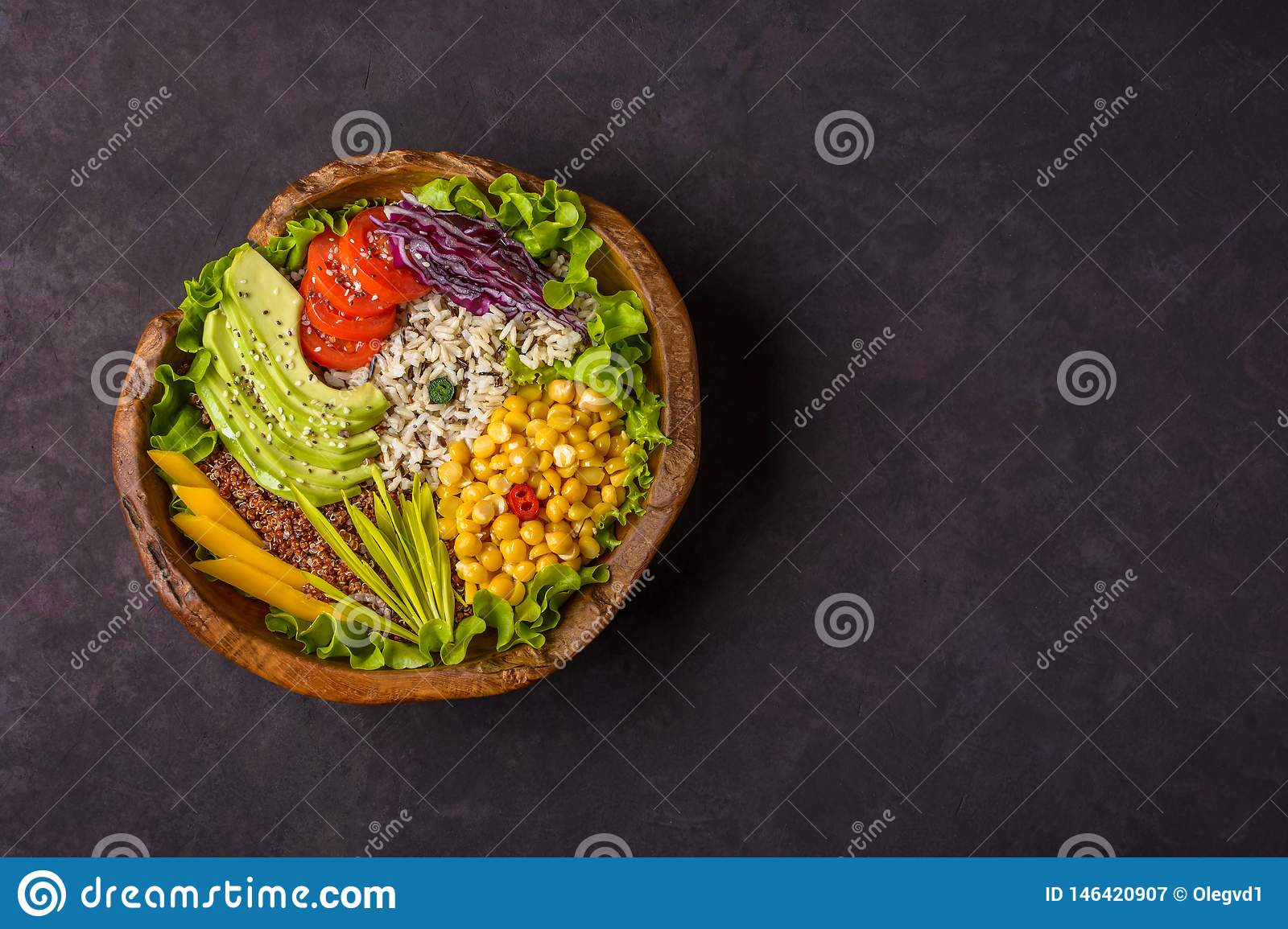 Wooden bowl with chickpea, avocado, wild rice, quinoa, tomatoes, greens, cabbage, lettuce on dark stone background. Vegetarian