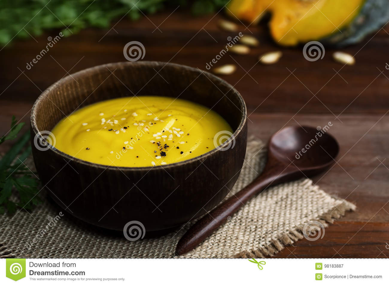 Wooden bowl of vibrant yellow pumpkin soup with spoon on table