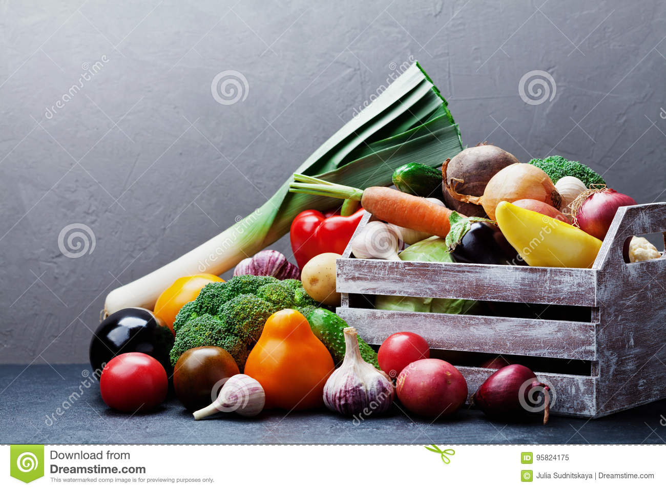 Wooden box with autumn harvest farm vegetables and root crops on dark kitchen table. Healthy and organic food.