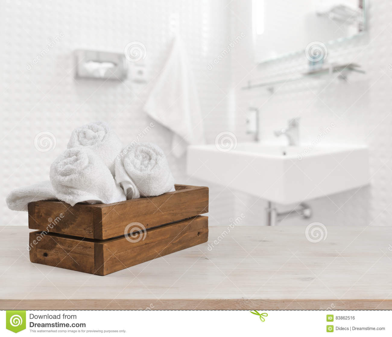 Wooden box with white spa towels on blurred bathroom background