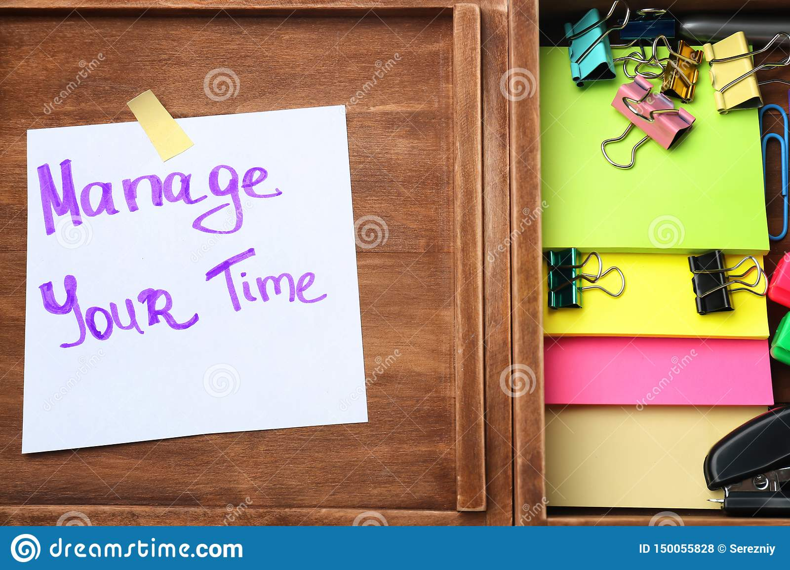 Wooden box with with written phrase  Manage your time   on paper sheet and stationery. Time management concept