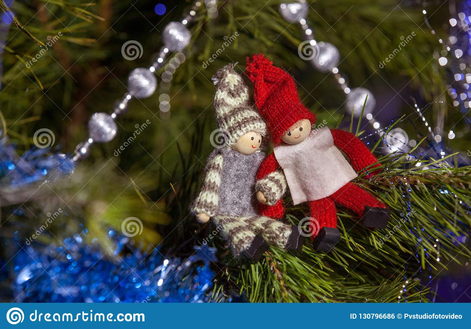 Wooden boy and girl figurines on the Christmas tree branch. Christmas decor.
