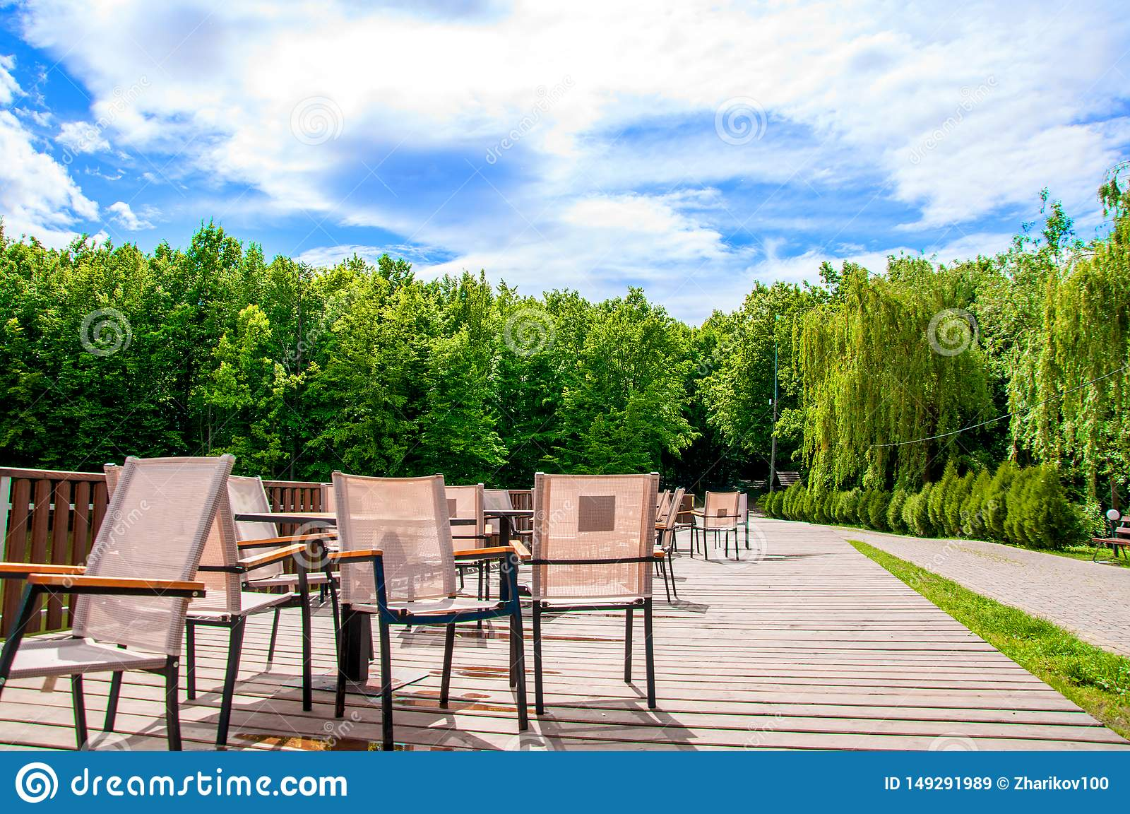Wooden bridge with a fence on which tables and chairs are located. Summer cafe. It`s summer outside. The sun is shining.